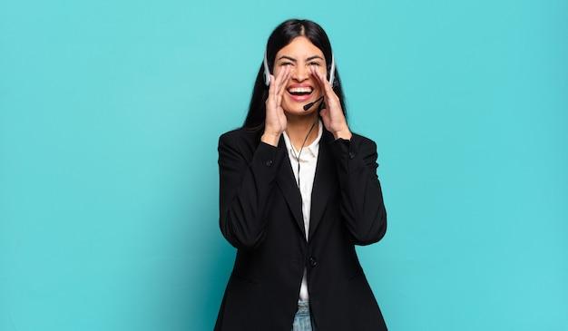 Jonge spaanse telemarketeervrouw die zich blij, opgewonden en positief voelt, een grote schreeuw geeft met de handen naast de mond, roept