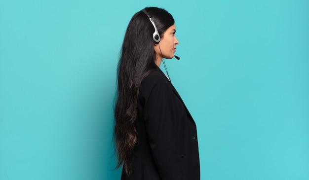 Jonge spaanse telemarketeervrouw op profielweergave die ruimte vooruit wil kopiëren, denken, fantaseren of dagdromen