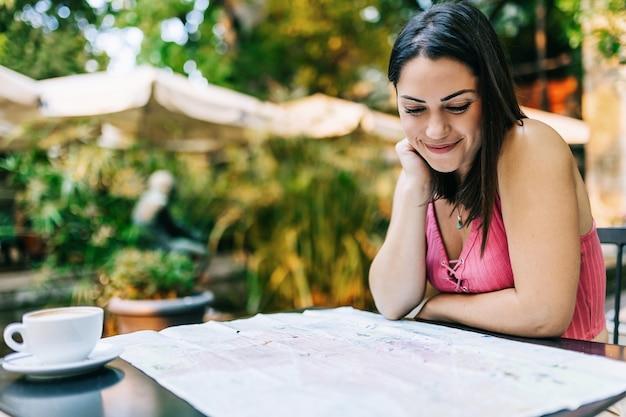 Jonge spaanse toerist die een kaart zoekt terwijl hij in een café zit. trendy vrouw die een smartphone gebruikt terwijl ze alleen reist en op zoek is naar nieuwe lokale plaatsen - zomervakantie en concept voor reizen in europa