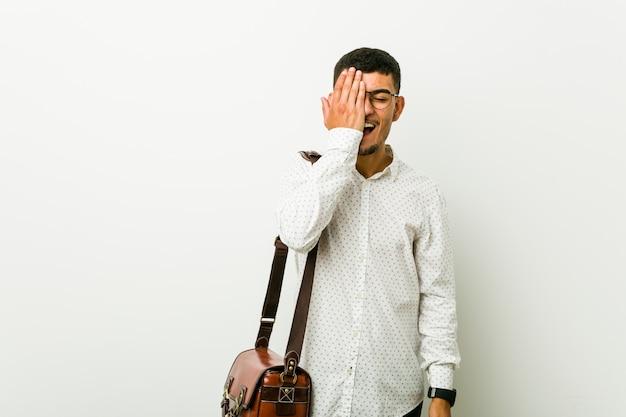 Jonge spaanse toevallige bedrijfsmens die pret heeft die de helft van gezicht behandelt met palm.