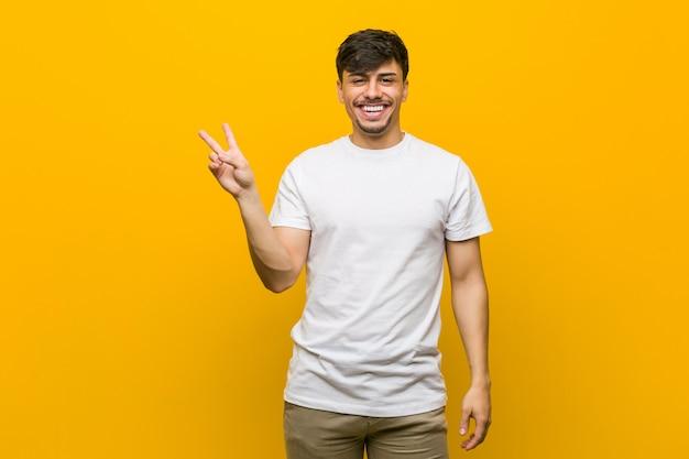Jonge spaanse toevallige mens blij en onbezorgd tonend een vredessymbool met vingers.