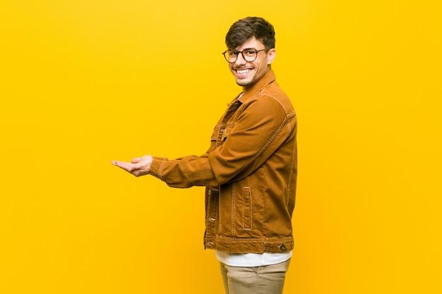 Jonge spaanse toevallige mens die een exemplaarruimte op een palm houdt.