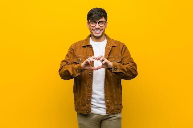 Jonge spaanse toevallige mens die en een hartvorm met handen glimlacht toont.