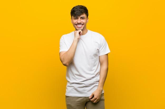 Jonge spaanse toevallige mens die gelukkig en zeker, wat betreft kin met hand glimlacht.