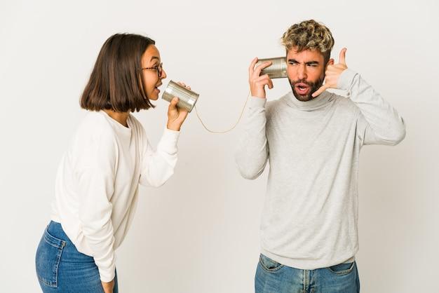 Jonge spaanse vrienden die door een blikjessysteem praten en een mobiel telefoongebaar met vingers tonen.