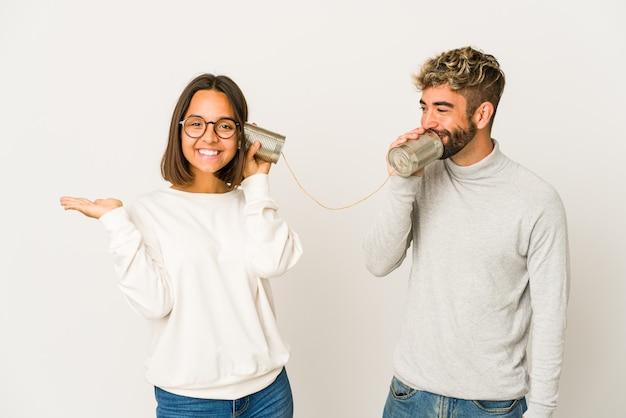 Jonge spaanse vrienden die door een blikjessysteem spreken dat een exemplaarruimte op een palm toont en een andere hand op taille houdt.