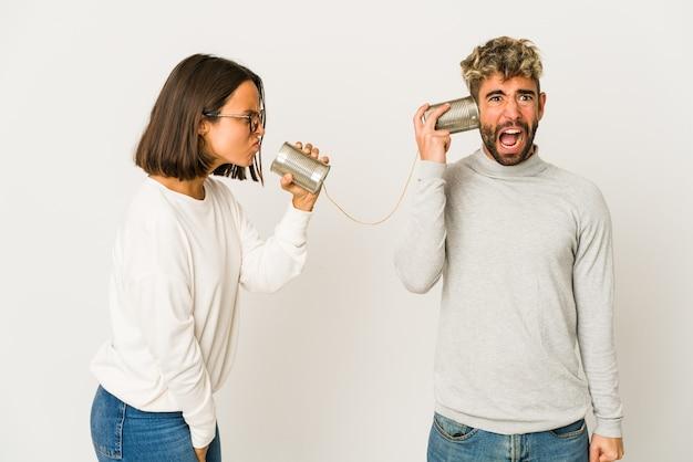 Jonge spaanse vrienden die door een blikjesysteem praten, schreeuwen erg boos en agressief.