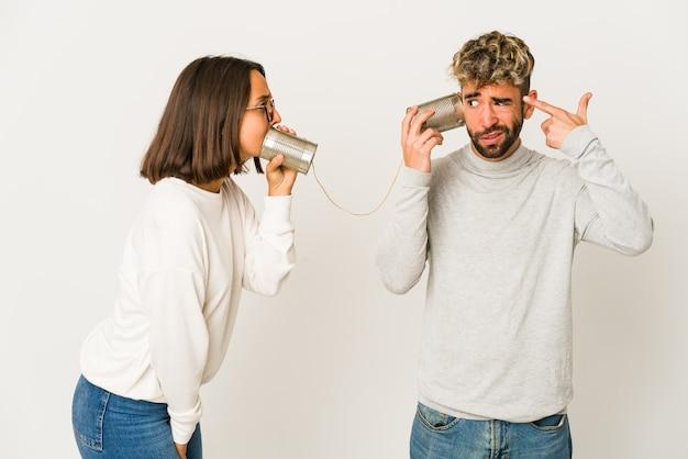 Jonge spaanse vrienden die door een blikjesysteem spreken die een teleurstellinggebaar met wijsvinger tonen