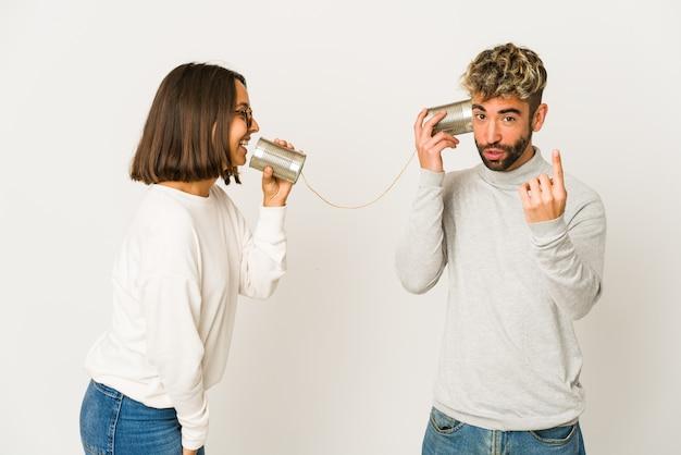 Jonge spaanse vrienden praten door een blikjes systeem en wijzen met de vinger naar je alsof ze uitnodigen om dichterbij te komen