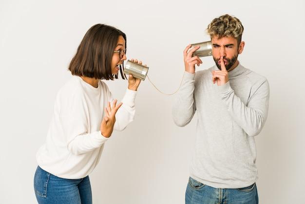 Jonge spaanse vrienden praten via een blikjes systeem een geheim bewaren of vragen om stilte.