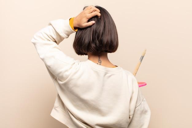 Jonge spaanse vrouw denken of twijfelen, hoofd krabben, zich verbaasd en verward voelen, achter- of achteraanzicht