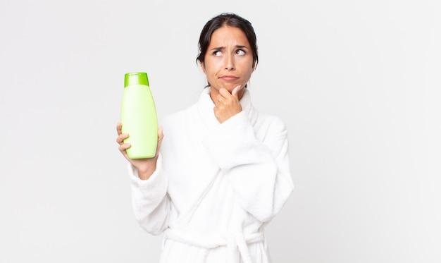 Jonge spaanse vrouw denkt, voelt zich twijfelachtig en verward, draagt een badjas en houdt een shampoo vast