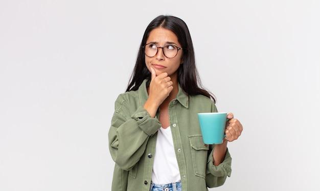 Jonge spaanse vrouw denkt, voelt zich twijfelachtig en verward en houdt een koffiemok vast