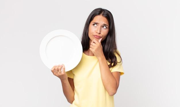 Jonge spaanse vrouw denkt, voelt zich twijfelachtig en verward en houdt een leeg bord vast