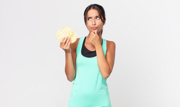 Jonge spaanse vrouw denkt, voelt zich twijfelachtig en verward. fitness dieet concept