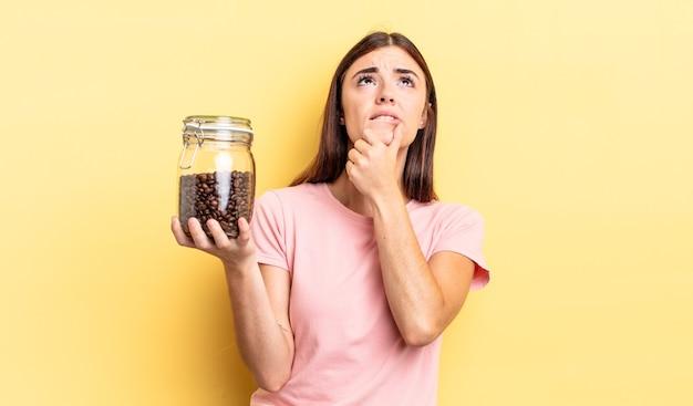 Jonge spaanse vrouw denkt, voelt zich twijfelachtig en verward. koffiebonen concept