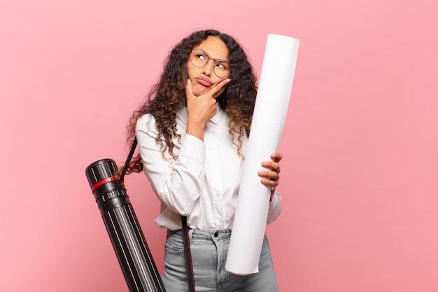 Jonge spaanse vrouw denkt, voelt zich twijfelachtig en verward, met verschillende opties, zich afvragend welke beslissing ze moet nemen. architect concept