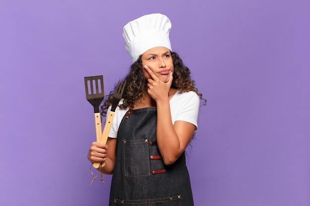 Jonge spaanse vrouw denkt, voelt zich twijfelachtig en verward, met verschillende opties, zich afvragend welke beslissing ze moet nemen. barbecue chef-kok concept