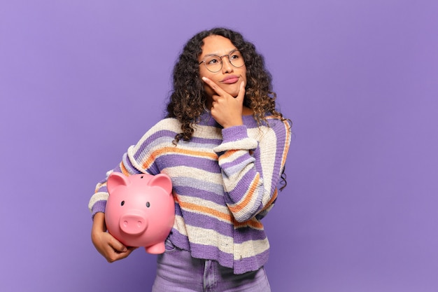 Jonge spaanse vrouw denkt, voelt zich twijfelachtig en verward, met verschillende opties, zich afvragend welke beslissing ze moet nemen. spaarvarken concept