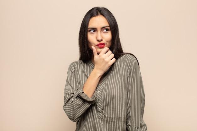 Jonge spaanse vrouw denkt, voelt zich twijfelachtig en verward, met verschillende opties, zich afvragend welke beslissing ze moet nemen
