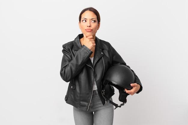 Jonge spaanse vrouw denkt, voelt zich twijfelachtig en verward. motorrijder concept