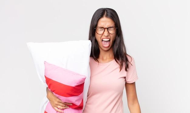 Jonge spaanse vrouw die agressief schreeuwt, er erg boos uitziet terwijl ze een pyjama draagt en een kussen vasthoudt
