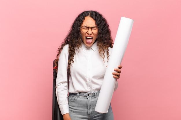 Jonge spaanse vrouw die agressief schreeuwt, erg boos, gefrustreerd, verontwaardigd of geïrriteerd kijkt en nee schreeuwt. architect concept