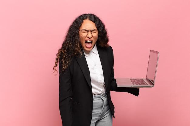 Jonge spaanse vrouw die agressief schreeuwt, erg boos, gefrustreerd, verontwaardigd of geïrriteerd kijkt en nee schreeuwt. laptopconcept