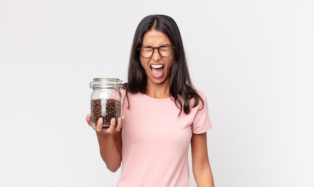 Jonge spaanse vrouw die agressief schreeuwt, erg boos kijkt en een fles koffiebonen vasthoudt