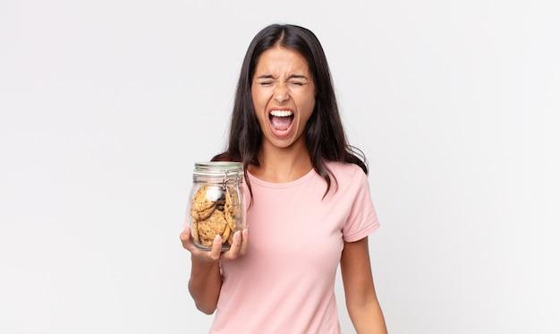 Jonge spaanse vrouw die agressief schreeuwt, erg boos kijkt en een glazen fles met koekjes vasthoudt