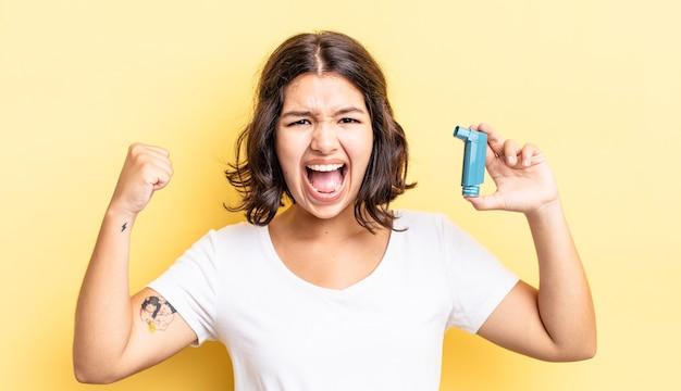 Jonge spaanse vrouw die agressief schreeuwt met een boze uitdrukking. astma concept