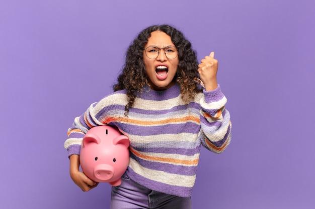 Jonge spaanse vrouw die agressief schreeuwt met een boze uitdrukking of met gebalde vuisten om succes te vieren. spaarvarken concept