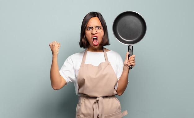 Jonge spaanse vrouw die agressief schreeuwt met een boze uitdrukking of met gebalde vuisten om succes te vieren