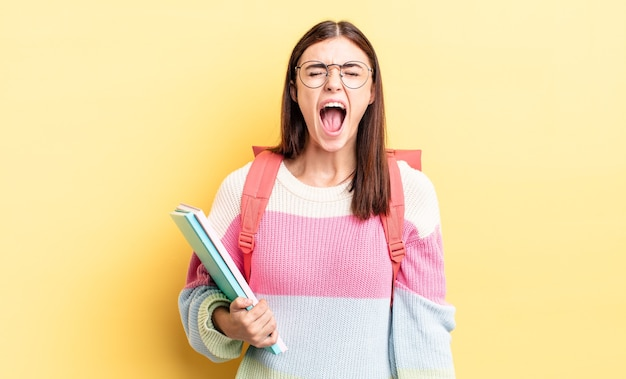 Jonge spaanse vrouw die agressief schreeuwt, ziet er erg boos uit. studentenconcept