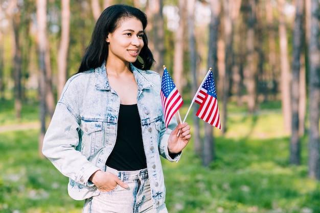 Jonge spaanse vrouw die amerikaanse vlaggen houdt