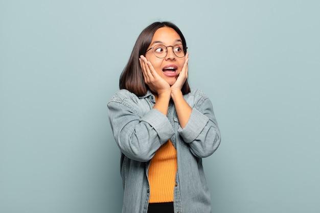 Jonge spaanse vrouw die blij, opgewonden en verrast voelt, naar de zijkant kijkend met beide handen op het gezicht