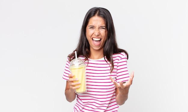 Jonge spaanse vrouw die boos, geïrriteerd en gefrustreerd kijkt en een vanila smoothy milkshake vasthoudt