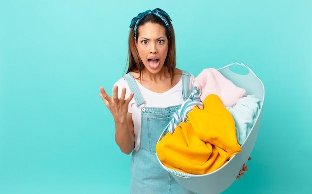 Jonge spaanse vrouw die boos, geïrriteerd en gefrustreerd kijkt en kleren aan het wassen is