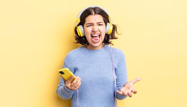 Jonge spaanse vrouw die boos, geïrriteerd en gefrustreerd kijkt. koptelefoon en smartphone concept