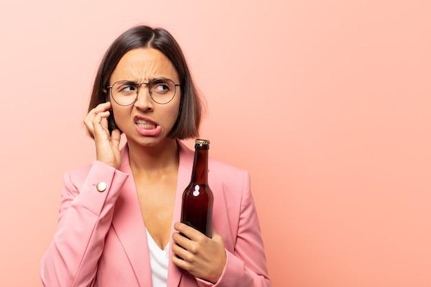 Jonge spaanse vrouw die boos, gestrest en geïrriteerd kijkt en beide oren bedekt met een oorverdovend geluid, geluid of luide muziek