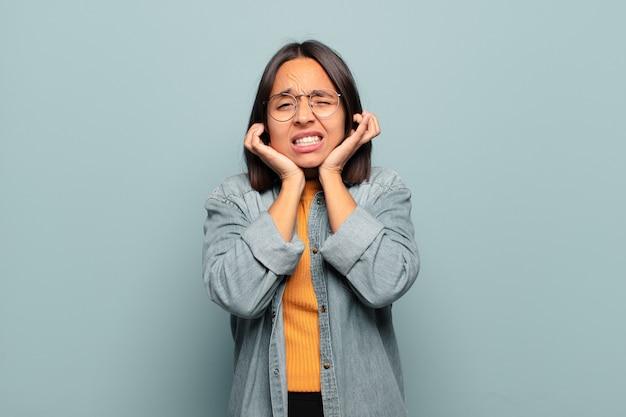 Jonge spaanse vrouw die boos, gestrest en geïrriteerd kijkt