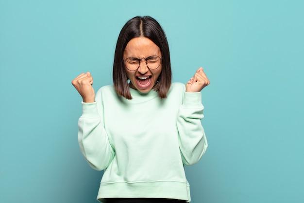 Jonge spaanse vrouw die buitengewoon blij en verrast kijkt, succes viert, schreeuwt en springt