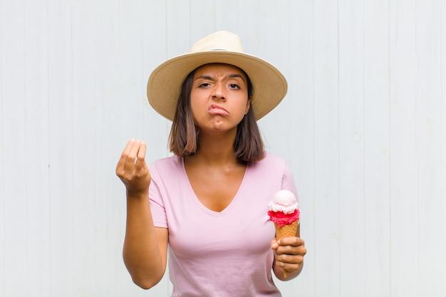 Jonge spaanse vrouw die capice of geldgebaar maakt, die u zegt uw schulden te betalen!