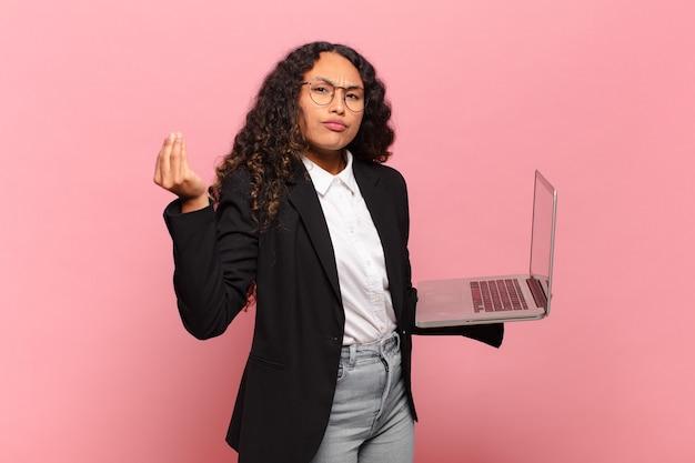 Jonge spaanse vrouw die capice of geldgebaar maakt en een laptop vasthoudt
