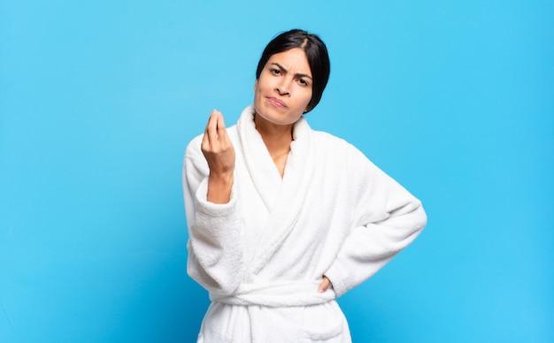 Jonge spaanse vrouw die capice of geldgebaar maakt en u vertelt om uw schulden te betalen!