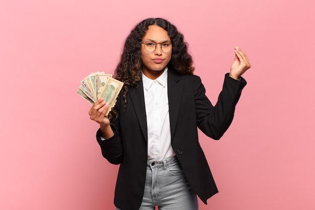 Jonge spaanse vrouw die capice of geldgebaar maakt en u vertelt uw schulden te betalen!. dollar biljetten concept