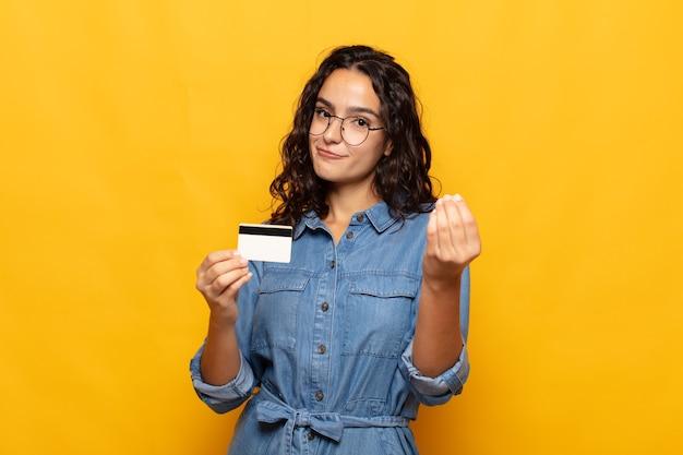 Jonge spaanse vrouw die capice of geldgebaar maakt en u vertelt uw schulden te betalen!