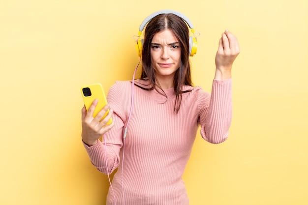 Jonge spaanse vrouw die capice of geldgebaar maakt en zegt dat je moet betalen. koptelefoon en telefoon concept