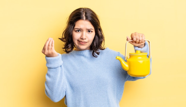 Jonge spaanse vrouw die capice of geldgebaar maakt en zegt dat je moet betalen theepot concept