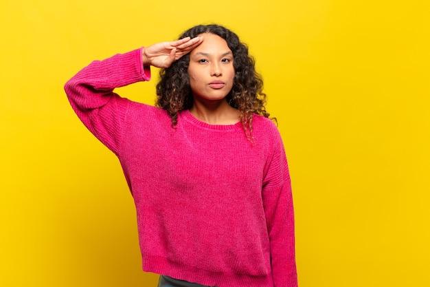 Jonge spaanse vrouw die de camera begroet met een militaire groet in een daad van eer en patriottisme, respect tonen